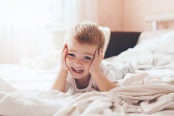 happy toddler lying on bed