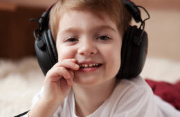 child listening to music through headphones Kinderling