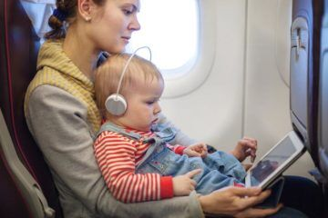 Baby sitting on mums lap on plane