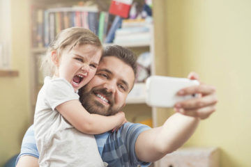 father poses for selfie with daughter stay-at-home dads do less work