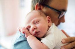 Dad cuddling a newborn on his shoulder