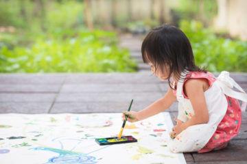 Little girl painting in the garden